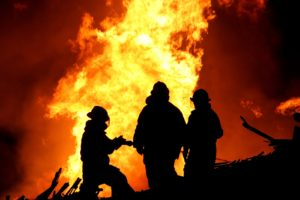 Silhouette of three firemen fighting a huge fire of burning timber